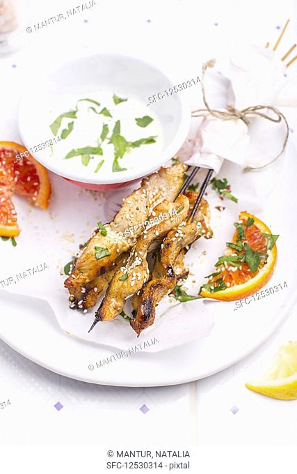 Lemony Marinated Chicken Skewers on a white plate, served with sesame seeds, orange pieces and fresh herbs