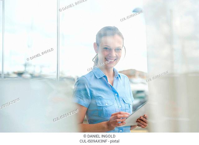 Portrait of woman through net curtain using digital tablet on marina, Majorca, Spain