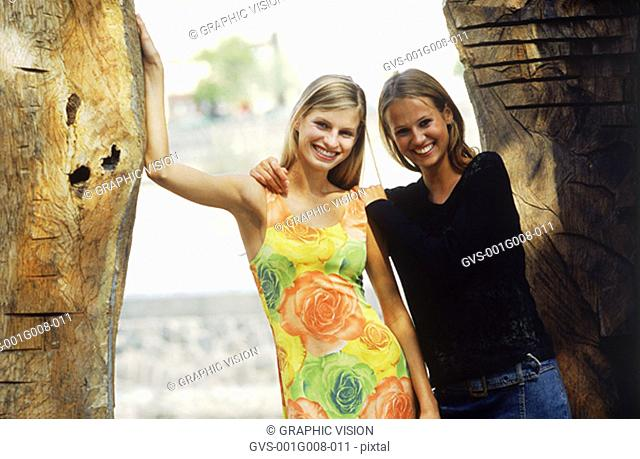 Portrait of two young women standing by a wall