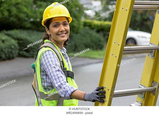 Portrait of happy Hispanic female lineman working on power line at site