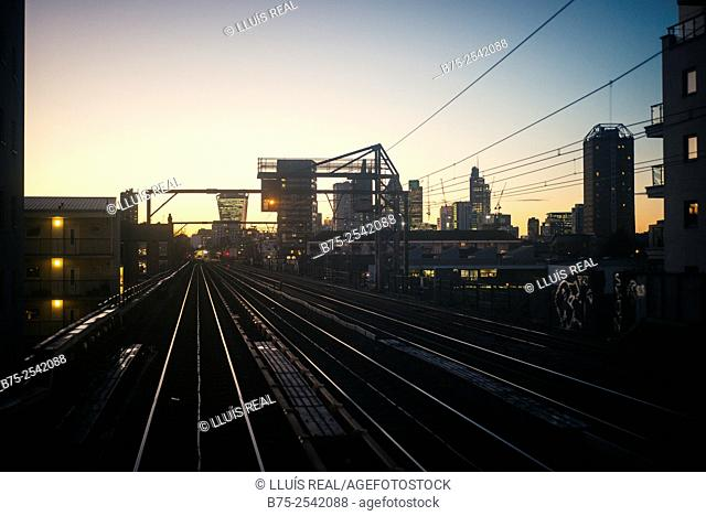 Urban view of the City of London at sunset from the DLR Docklands rails. Shadwell, London, England, UK, Europe