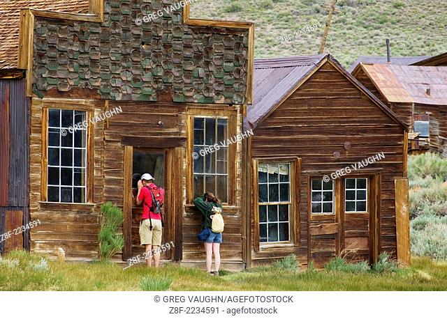 Couple looking through windows of abandoned house in Bodie State Historical Park ghost town; California.#D0406130