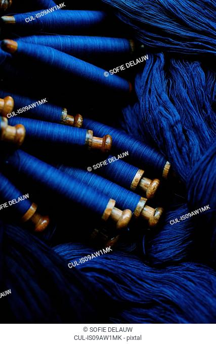 Overhead view of indigo threads and bobbins