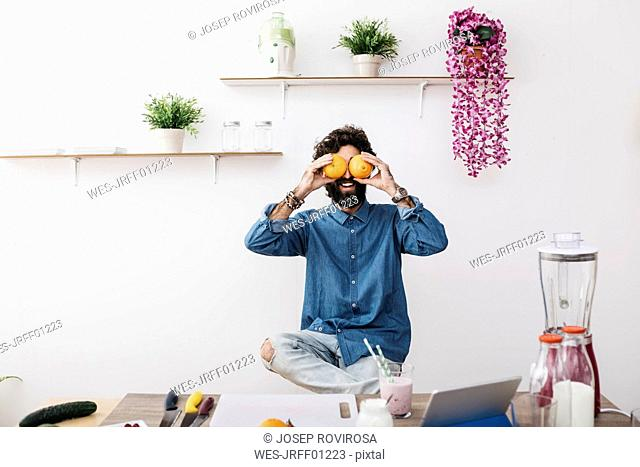 Laughing man covering his eyes with oranges