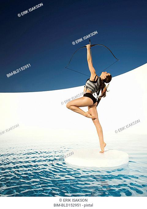 Caucasian woman aiming bow and arrow on ice floe