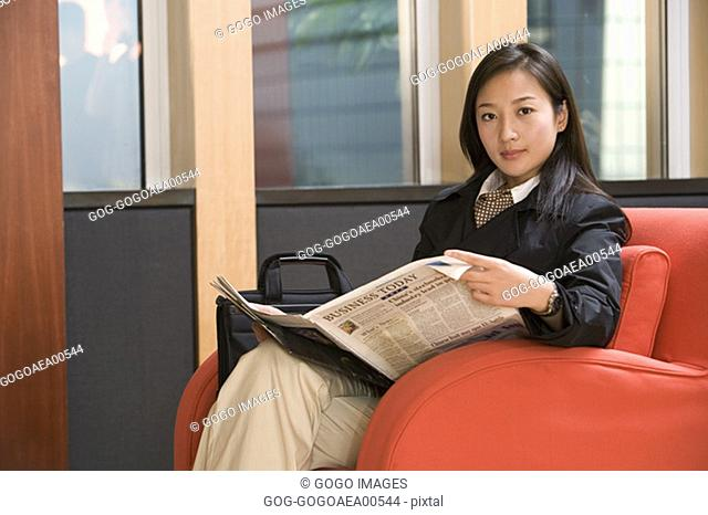 Businesswoman reading newspaper in armchair