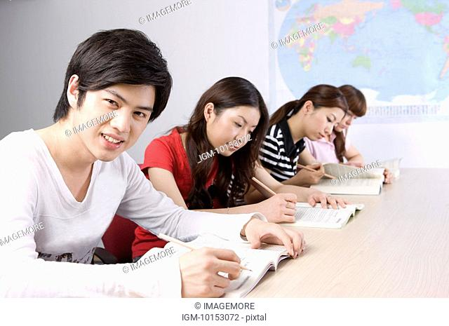 Four young college students sitting and studying in the classroom, Studying, Education