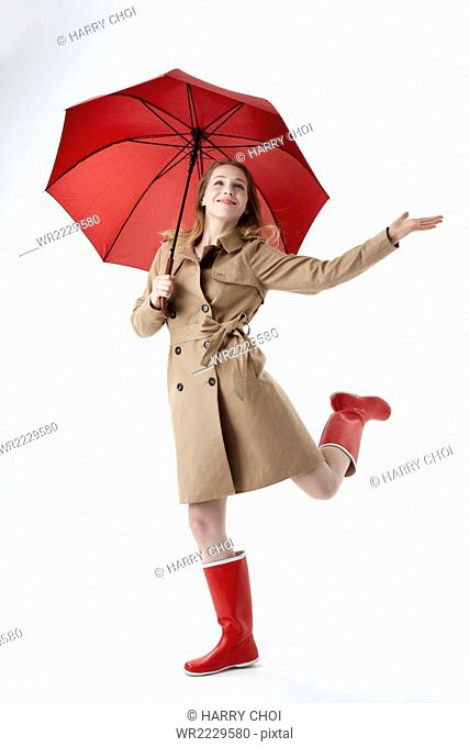 Young smiling woman wearing red umbrella, trenchcoat and red boots running looking up