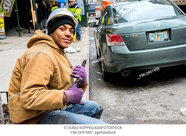 New York, USA. Young African American male sitting on the sidewalk, down town Manhattan, making sings in street language