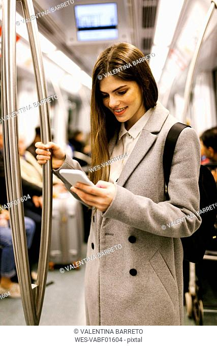 Spain, Barcelona, young businesswoman using cell phone in underground train