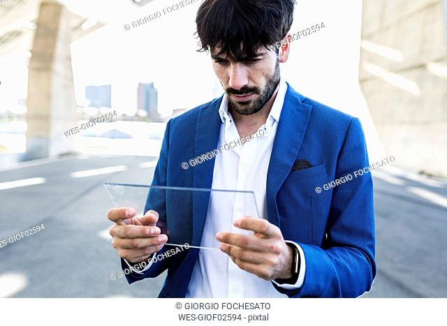 Young businessman holding futuristic portable device