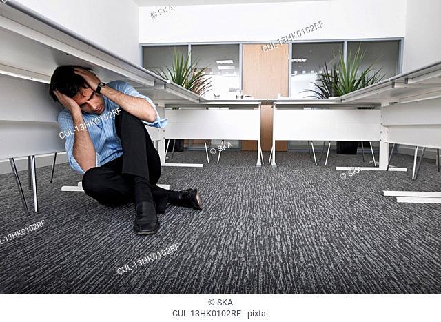 man hiding under desk