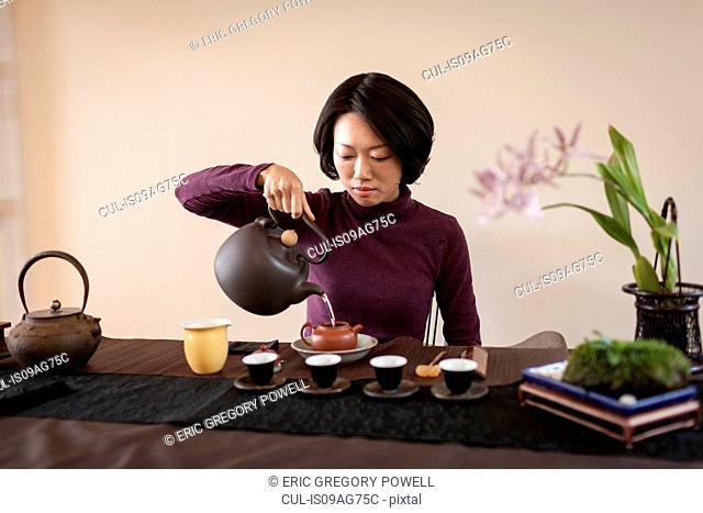 Mid adult woman performing traditional Chinese tea ceremony