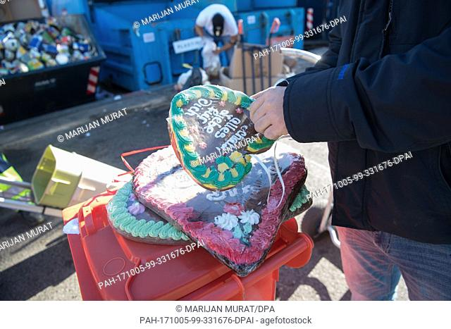 A showman removing the foil from a gingerbread heart in order to dispose of the constituents in their respective garbage bins in Stuttgart, Germany
