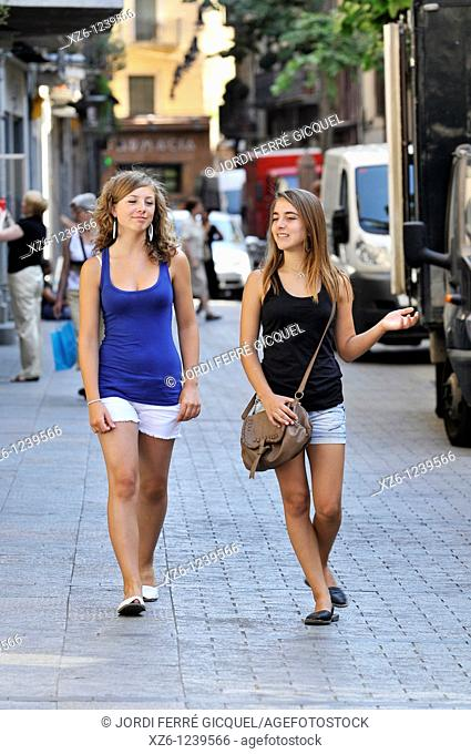 Two girls walking on a street in Girona, Catalonia, Spain, Europe