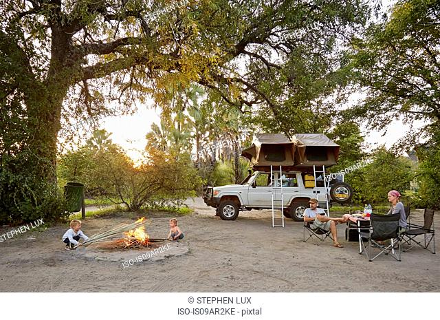 Off road vehicle parked, family relaxing around camp fire, Nata, Makgadikgadi, Botswana