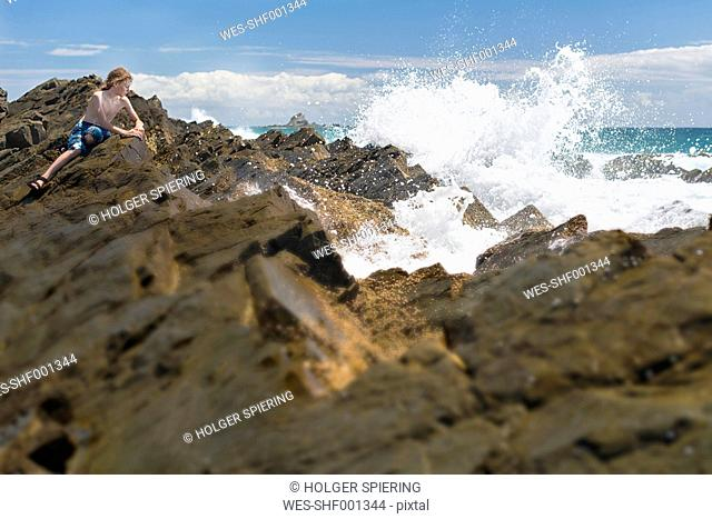 Australia, New South Wales, Byron Bay, Broken Head nature reserve, boy on rocks with breaking waves in front