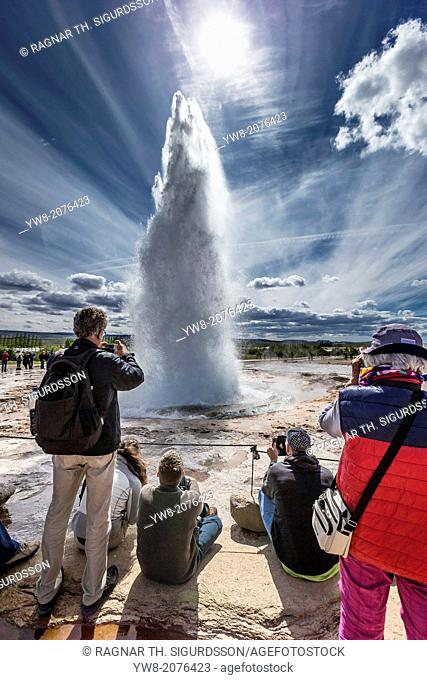 Tourist taking pictures of Strokkur Gesyer erupting, Iceland
