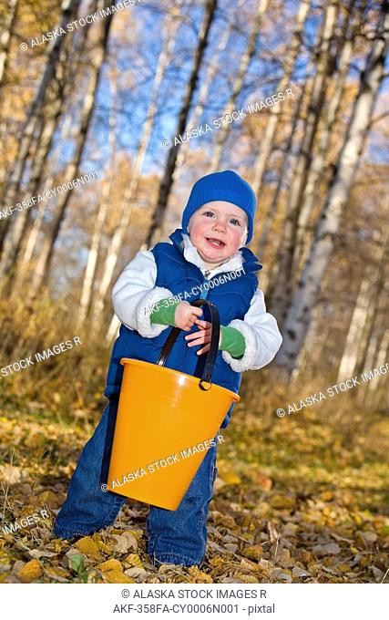 Young girl toddler playing in the Fall leaves carring a orange bucket in a forested area of Anchorage in Southcentral Alaska