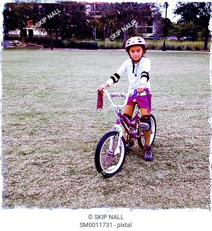 A 7 year old girl looking at camera on her bicycle