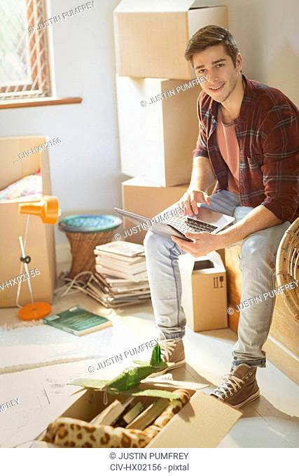 Portrait smiling young man using laptop surrounded by moving boxes in new apartment