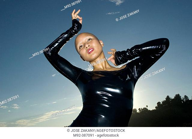 Diva in Latex With Dark Sky. This shot was made in Grifith Park, Los Angeles, California. On September 9, 2004. The model actually shaved her head for this...