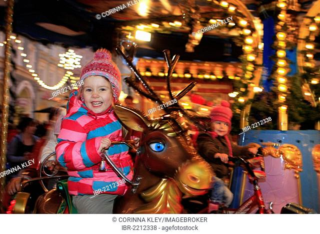 Little girl, three years, riding on a carousel at a Christmas market