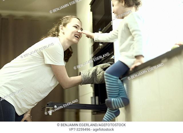 laughing mother and toddler at baking oven in kitchen at home, in Munich, Germany