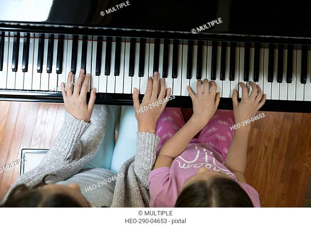 Overhead view sisters playing piano