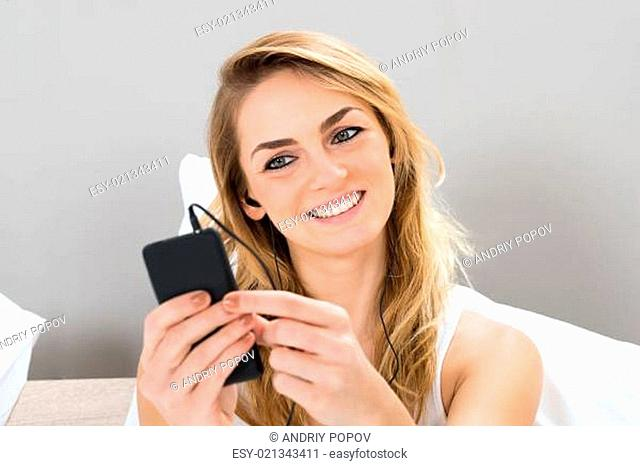 Happy Young Woman Sitting On Bed Listening Music