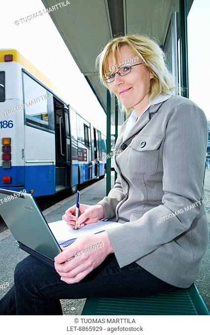 Working women. A woman writing notes at a bus stop