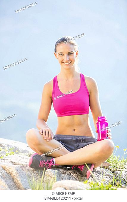 Caucasian woman sitting with water bottle