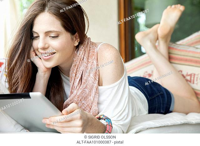 Young woman lying on stomach, looking at digital tablet