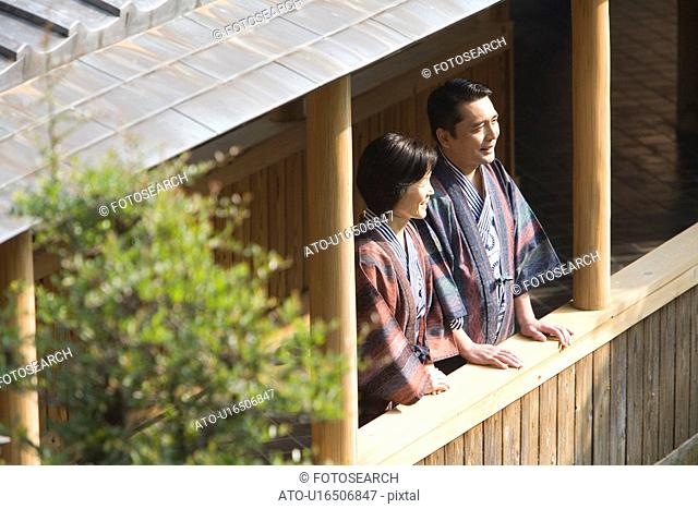 Mature Adult Couple Standing at a Hallway and Looking Outside, Side View, High Angle View, Waist Up