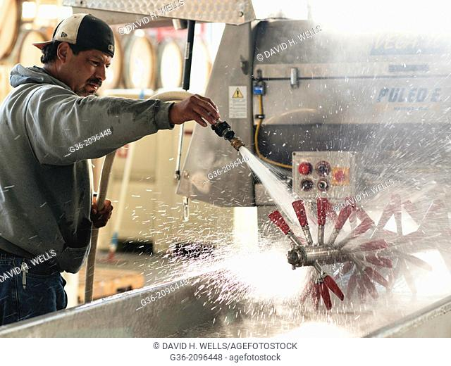 Man cleaning machine with a water hose at winery, Paso Robles, California