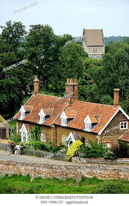 Red brick cottages with dormer windows and gardens and Church of St. Lawrence in village of Castle Rising, Norfolk, England