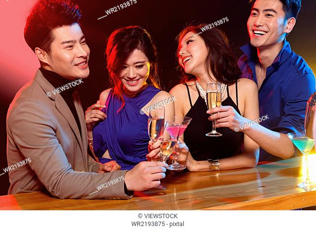 Young men and women drink in the bar