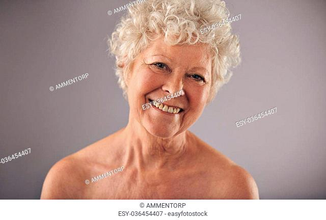 Headshot of a beautiful mature woman isolated on grey background. Shirtless caucasian old female smiling at camera