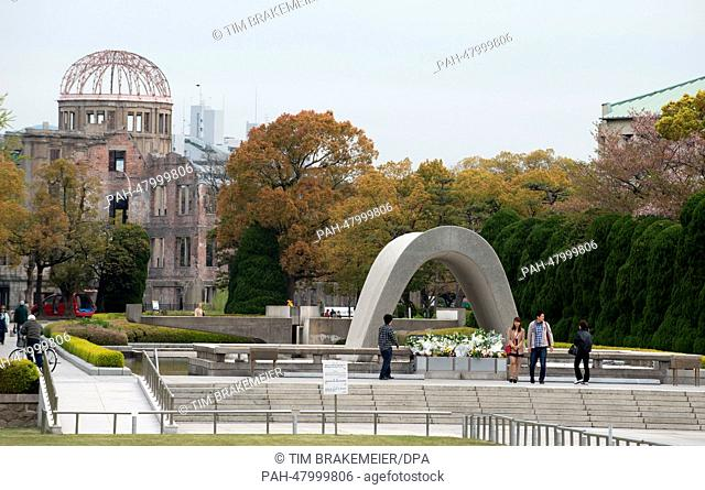 People stand in front of the cenotaph at the Hiroshima Peace Memorial Park in Hiroshima, Japan, 12 April 2014. The A-Bomb Dome