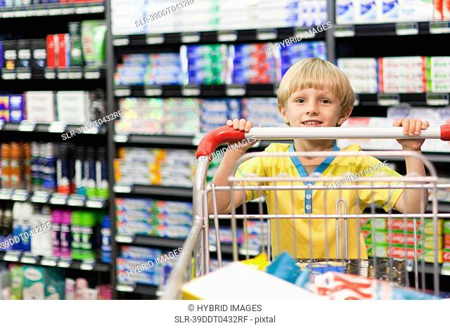 Boy pushing cart in grocery store