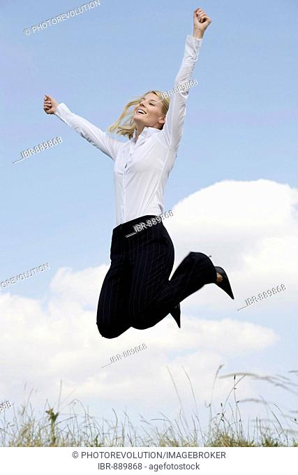 Young blonde woman wearing business clothing jumping in front of a blue sky, outstretched arms