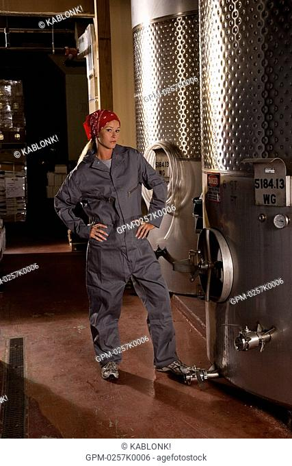 Winery worker standing next to wine vats