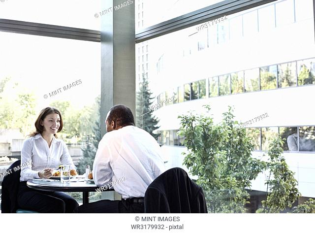 Business woman and man in an informal lunch meeting at a table in a open lobby area