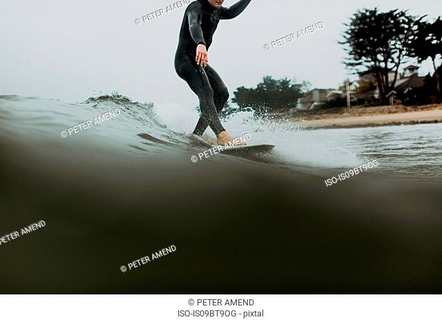 Young male surfer surfing on calm sea, Ventura, California, USA