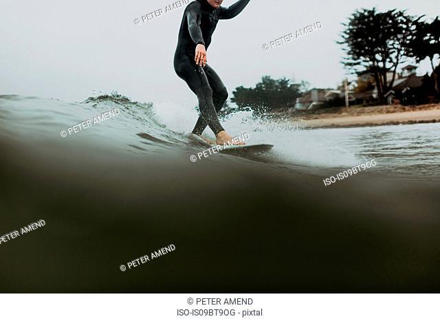 Young male surfer surfing on calm sea, Ventura, California, USA