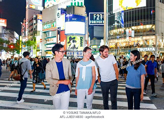 Caucasian couple enjoying sightseeing with Japanese friends in Tokyo, Japan