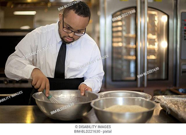 Mixed race chef with down syndrome cooking in restaurant