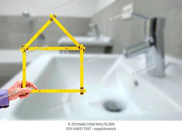 Meterstab symbolisch als Modellhaus im Badezimmer