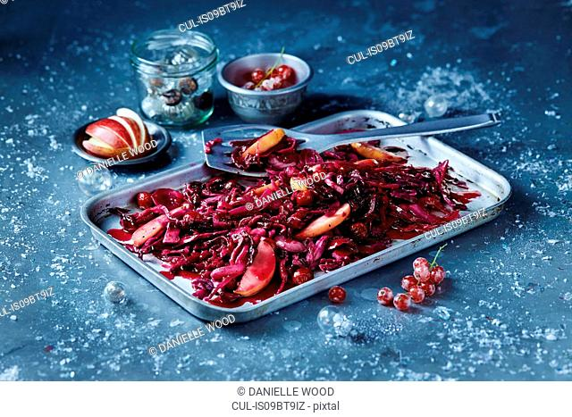 Roasted red cabbage and sliced apple in baking tin, seasonal Christmas food