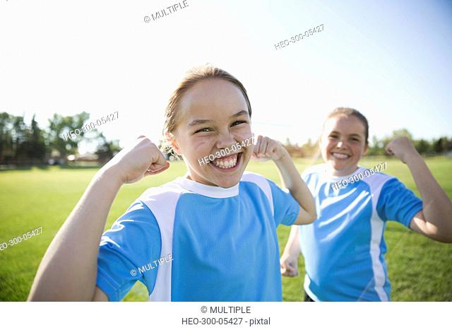 Portrait enthusiastic middle school girl soccer players flexing biceps on sunny field